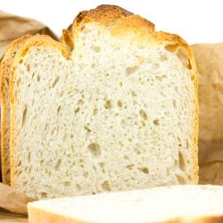 Sliced Whole Grain Bread in a Paper Bag Isolated on White